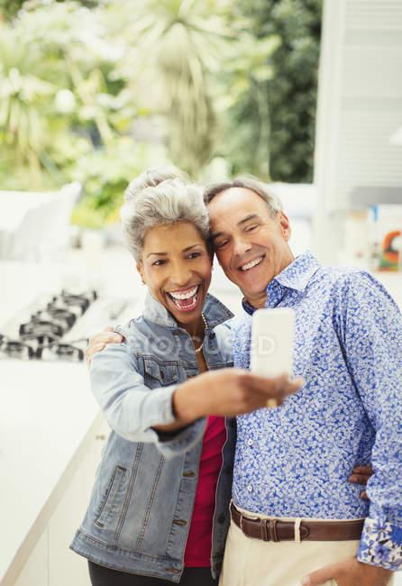 Enthusiastic mature couple taking selfie — Stockfoto