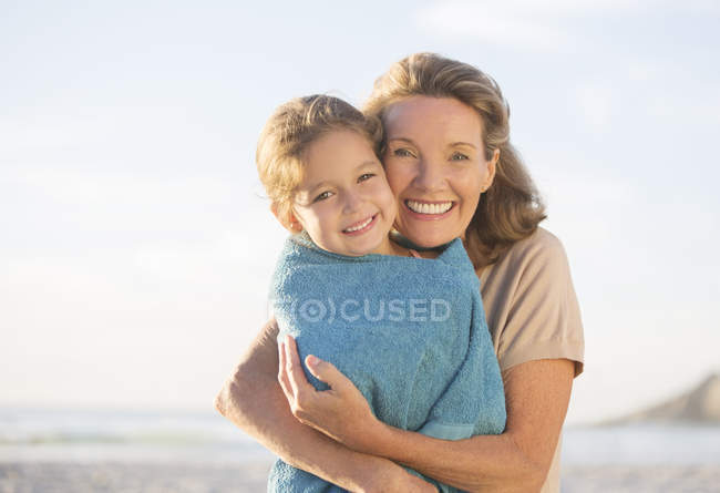 Grandmother and granddaughter hugging on beach — Stock Photo