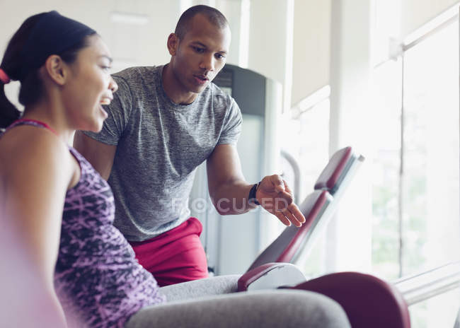 Personal trainer guiding woman on exercise equipment at gym — Stock Photo