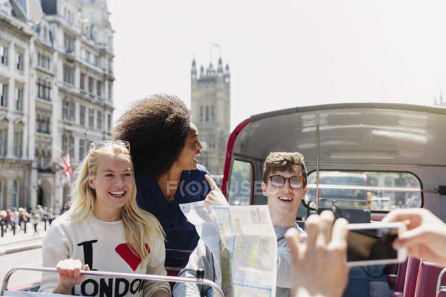 Freunde mit Karte fahren Doppeldeckerbus, London, Vereinigtes Königreich — Stockfoto