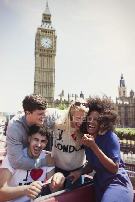 Amigos entusiastas andando de ônibus de dois andares abaixo Big Ben clocktower, Londres, Reino Unido — Fotografia de Stock