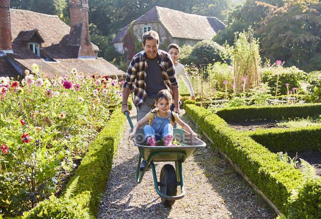 Père poussant fille dans brouette dans un jardin ensoleillé — Photo de stock