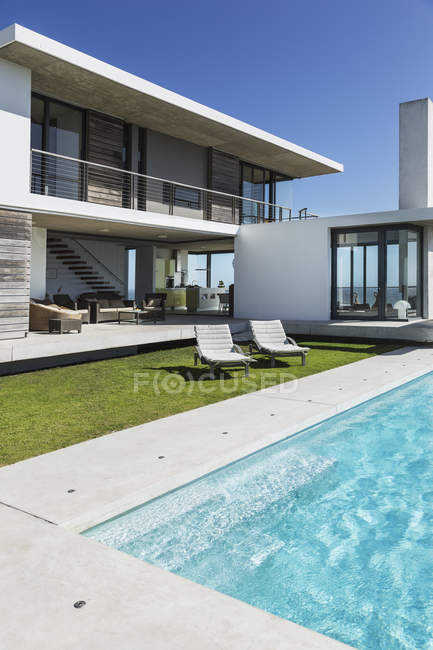 Lounge chairs and swimming pool outside modern house — Stock Photo
