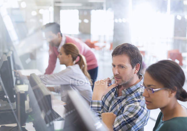 Étudiants à des ordinateurs dans la salle de classe de l'éducation des adultes — Photo de stock