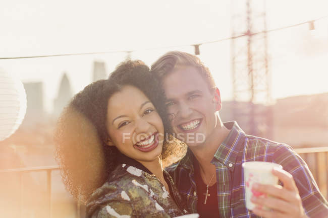 Portrait smiling young couple enjoying rooftop party — Stockfoto