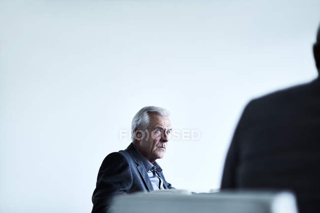 Serious senior businessman listening in meeting — Stock Photo