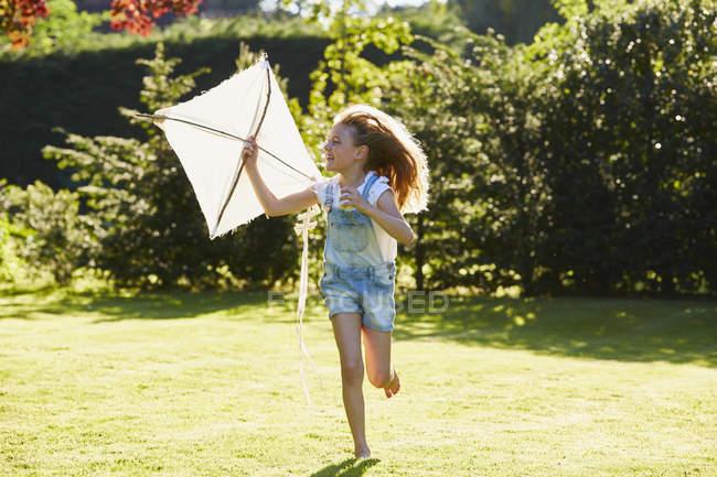 Girl running with kite in sunny garden — Stock Photo