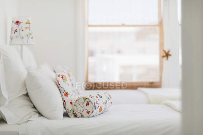 Closeup view of colorful pillows on white bed — Stock Photo