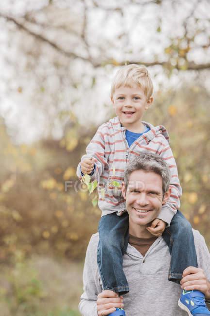 Retrato sonriente padre llevando a su hijo pequeño en hombros en el parque de otoño - foto de stock