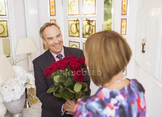 Mature man giving rose bouquet to wife — Stockfoto