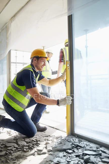 Строительный рабочий, используя инструмент уровня на строительной площадке — стоковое фото