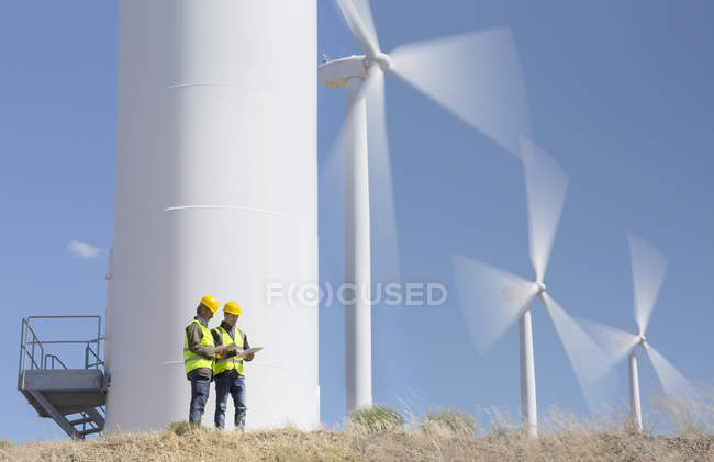 Workers talking by wind turbines in rural landscape — Stock Photo