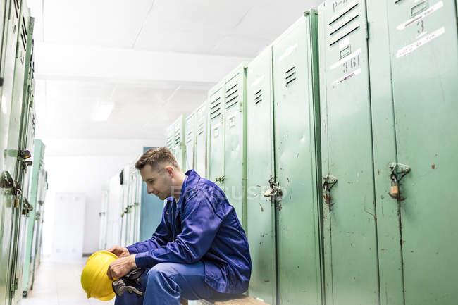 Trabalhador segurando o capacete no vestiário — Fotografia de Stock