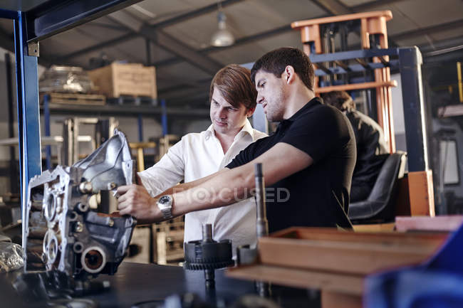Mechanic and customer examining part in auto repair shop — Stock Photo