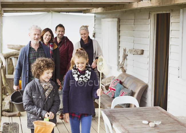 Familia de múltiples generaciones con redes y cubo en porche - foto de stock