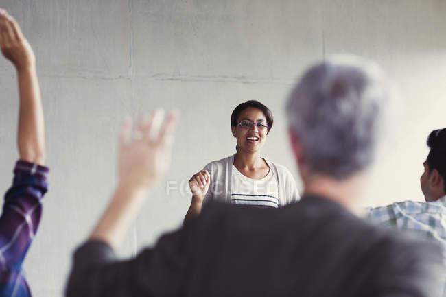 Lehrer fordert Studenten mit Handzeichen in Erwachsenenbildung Klassenzimmer — Stockfoto