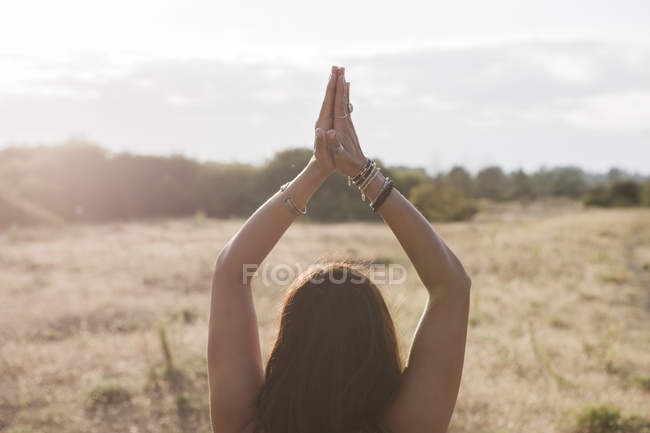Woman meditating with hands clasped overhead in sunny rural field — Stock Photo