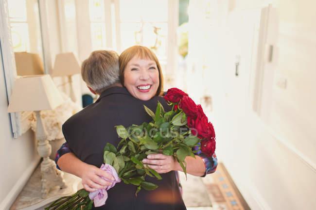 Glückliche Frauen empfangen rose Bouquet und Mann umarmt — Stockfoto