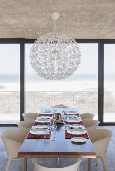 Set table in modern dining room overlooking ocean — Stock Photo