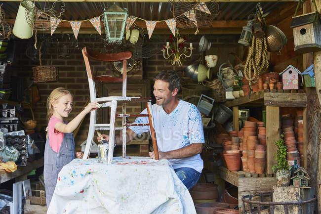Pai e filha cadeira de pintura em oficina — Fotografia de Stock