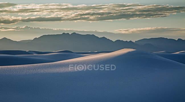 Montagnes silhouettées derrière une paisible dune de sable blanc, White Sands, Nouveau-Mexique, États-Unis — Photo de stock