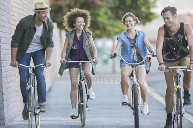 Friends riding bicycles on urban sidewalk — Stock Photo