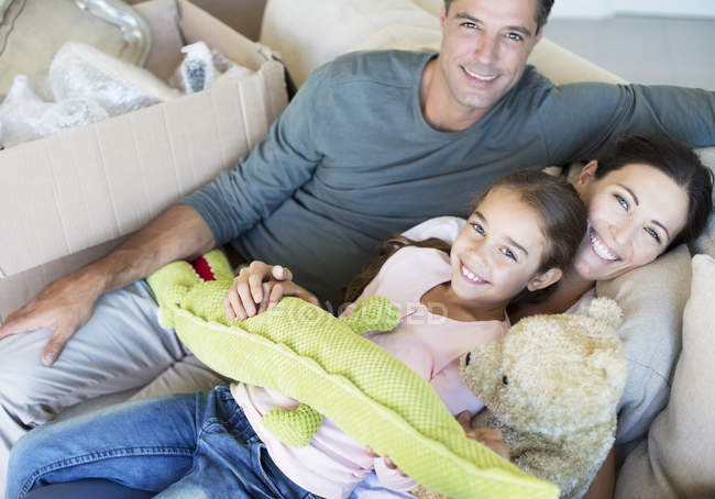 Portrait of smiling family with stuffed animals on sofa — Stockfoto