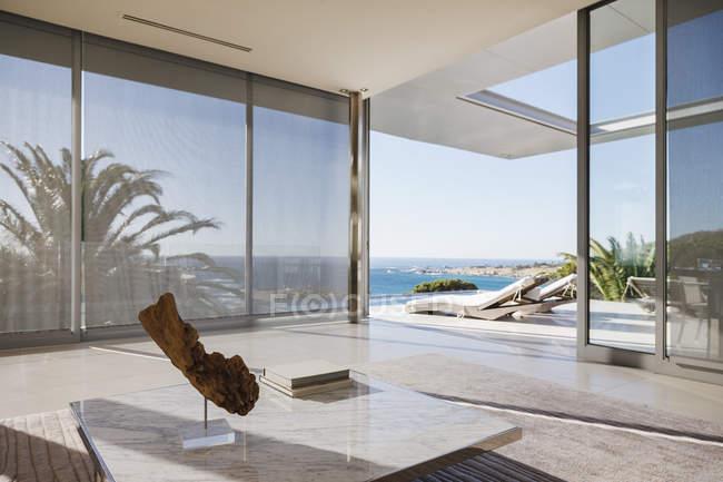 Modern living room and patio overlooking ocean — Stock Photo