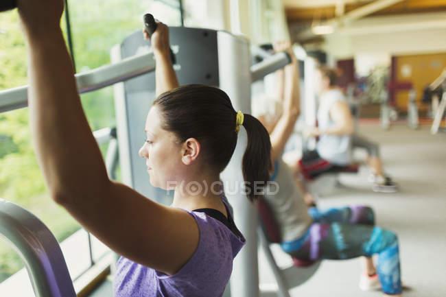 Konzentrierte sich Frau mit Trainingsgeräten im Fitnessstudio — Stockfoto