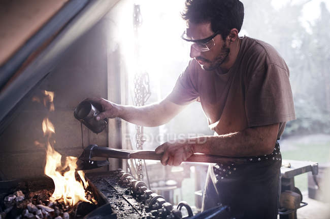 Blacksmith pouring liquid over tool at fire in forge — Stock Photo