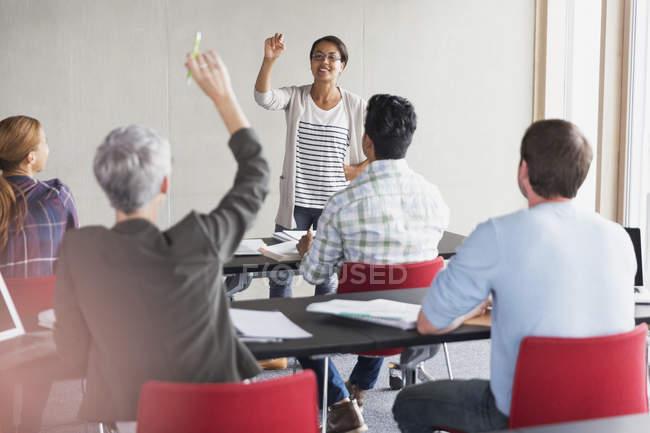 Enseignant en appelant sur l'étudiant avec la main levée dans la salle de classe de l'éducation des adultes — Photo de stock