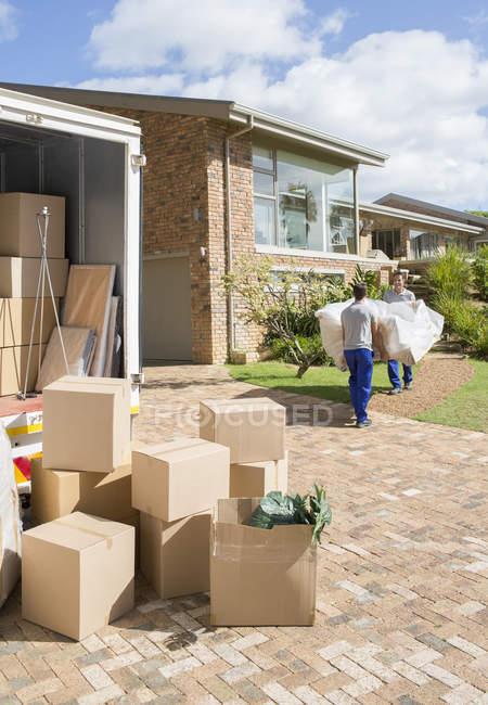 Déménageurs transportant sofa de fourgon de déménagement de maison neuve — Photo de stock