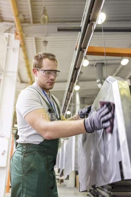 Worker sanding steel part in factory — Stock Photo