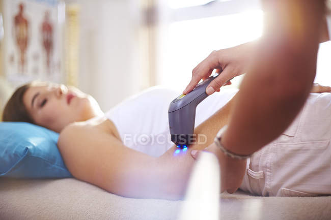 Physical therapist using ultrasound probe on woman arm — Stock Photo