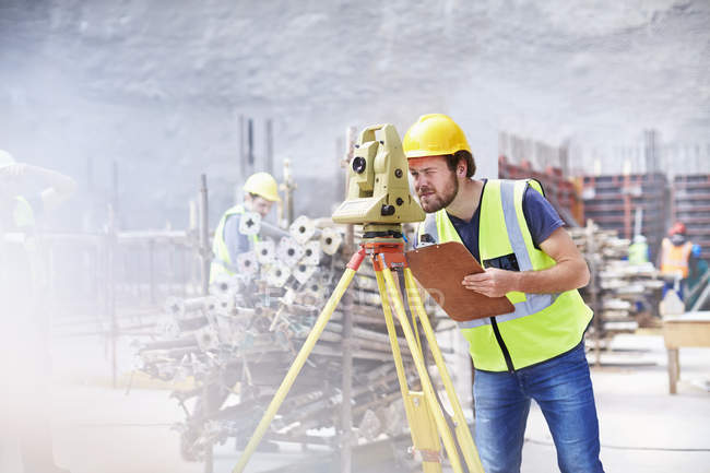 Engineer with clipboard using theodolite at construction site — Stock Photo