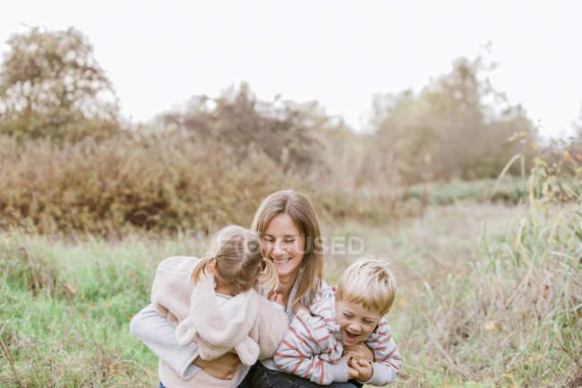 Mère et tout-petit enfants câlins dans le parc d'automne — Photo de stock