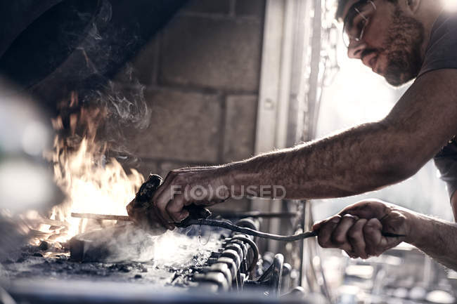 Blacksmith working over fire in forge — Stock Photo