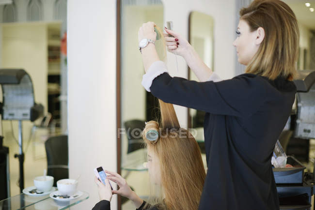 Coiffeur enveloppant les cheveux des clients dans les bigoudis dans le salon — Photo de stock