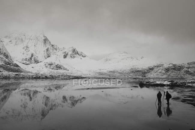 Photographers below snow covered mountains and calm bay, Norway — Stock Photo