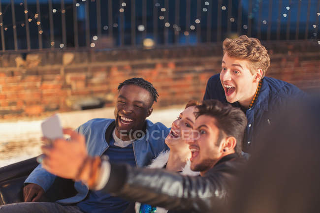 Enthusiastic young adults taking selfie at nighttime rooftop party — Fotografia de Stock