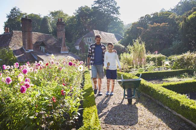 Padre e figlio camminano nel giardino soleggiato — Foto stock