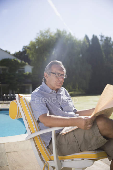 Happy man reading newspaper at poolside — Stock Photo