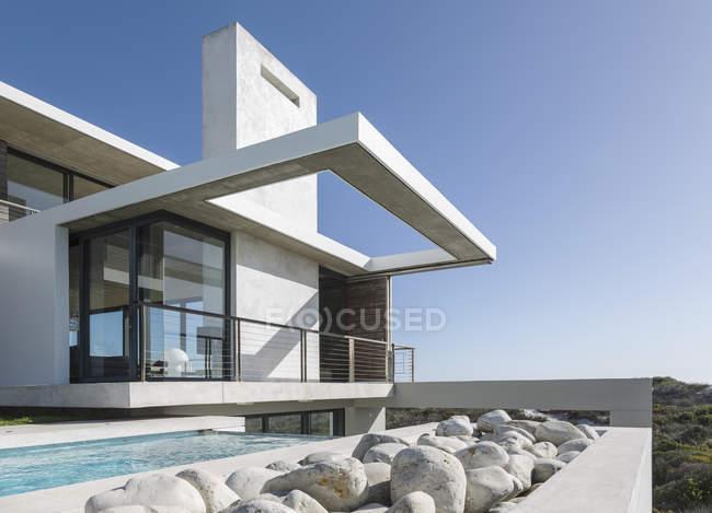 Rocks along lap pool outside modern house — Stock Photo