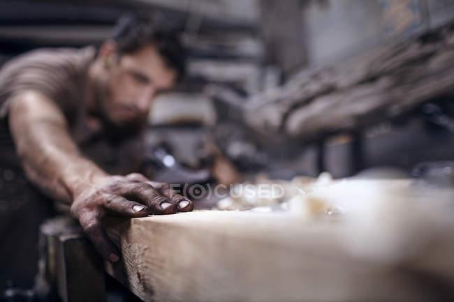 Craftsman chiseling wood in workshop — Stock Photo