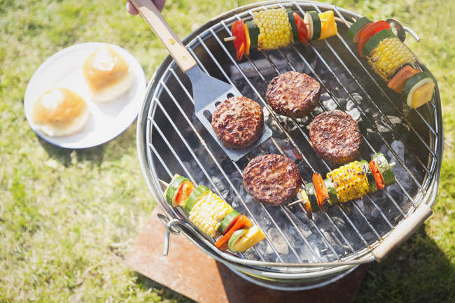 Overhead view of hamburgers and vegetable skewers on barbecue grill — Stock Photo