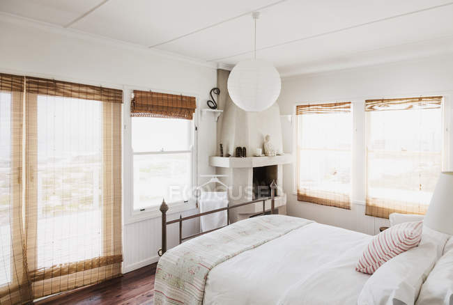 Reed curtains in white bedroom interior — Stock Photo