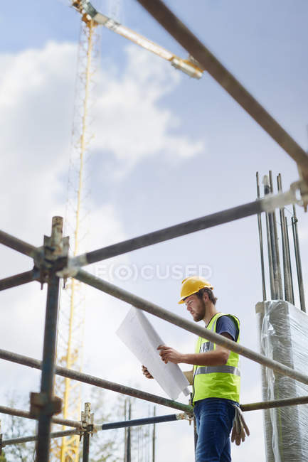 Engineer reviewing blueprints at high rise construction site — Stock Photo