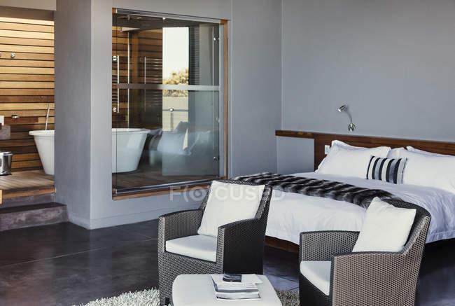 Кровати и кресла в современной спальни — стоковое фото