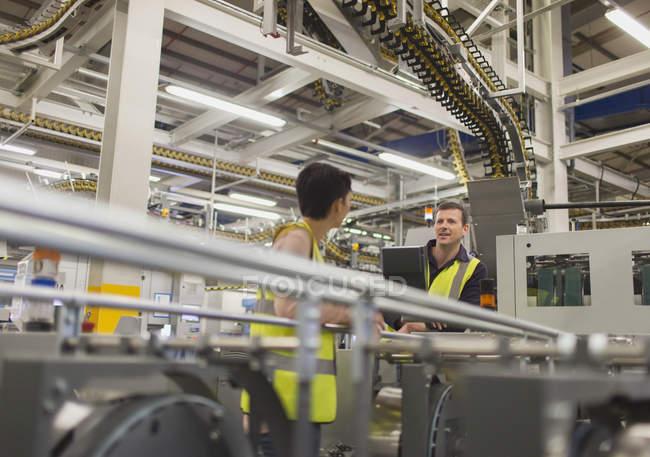 Arbeiter bei Maschinen in der Fabrik sprechen — Stockfoto