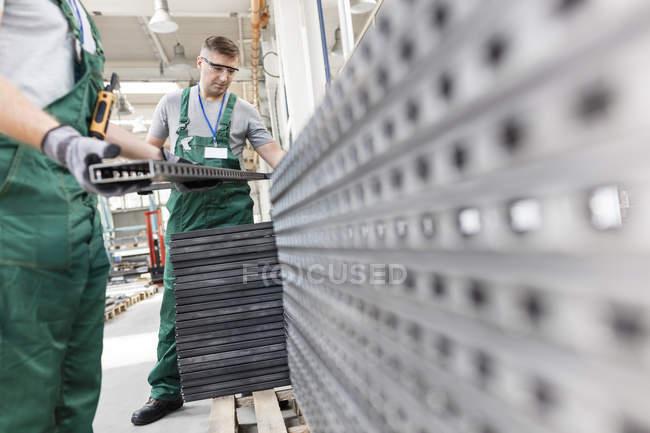 Trabalhadores, levantando as peças de aço em fábrica — Fotografia de Stock
